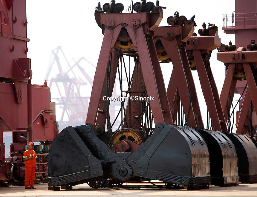 A dock worker inspects large diggers used to transport iron ore at one of the terminals of the Qingdao Port in Qingdao, China..13 Aug 2007