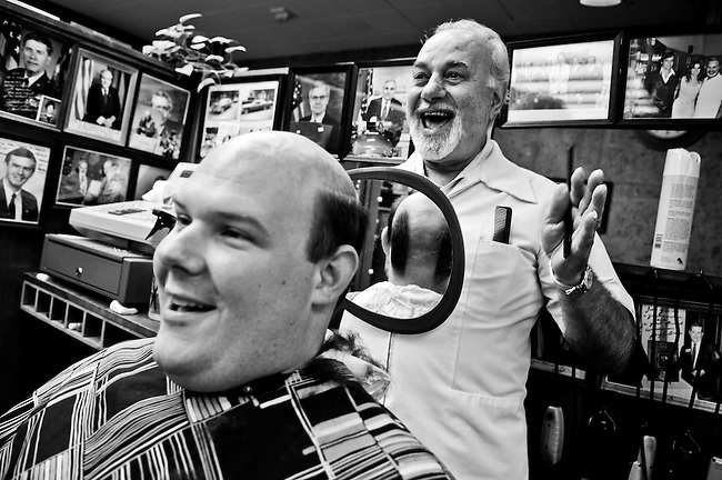 John Tomaszewski, communications director for Rep. Gus Bilirakis, R-Fla., gets a look at his new haircut by House barber Joe Q in the Rayburn House Office Building basement on Aug. 18, 2007. John got his head shaved, along with legislative director Jerry White, to show support for cancer research.