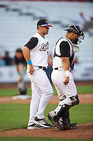 Quad Cities River Bandits pitching coach Chris Holt (20) and catcher Christian Correa (9) walk to the mound during a game against the Bowling Green Hot Rods on July 24, 2016 at Modern Woodmen Park in Davenport, Iowa.  Quad Cities defeated Bowling Green 6-5.  (Mike Janes/Four Seam Images)