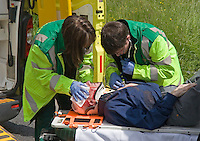 Ambulance Paramedic crew examining male patient on stretcher following RTC..This image may only be used to portray the subject in a positive manner..©shoutpictures.com..john@shoutpictures.com