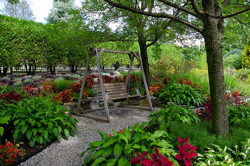 Wooden swing seat at Pineland garden with hastas and coleus in the shade, Maine, USA