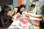 Education High School science lab male and female students wearing goggles doing lab, girls taking an active role