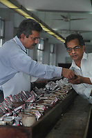 A tea tester shows his assistant the quality of the tea at the tea testing room of  J. Thomas ltd. company in Kolkata,  West Bengal, India, Arindam Mukherjee