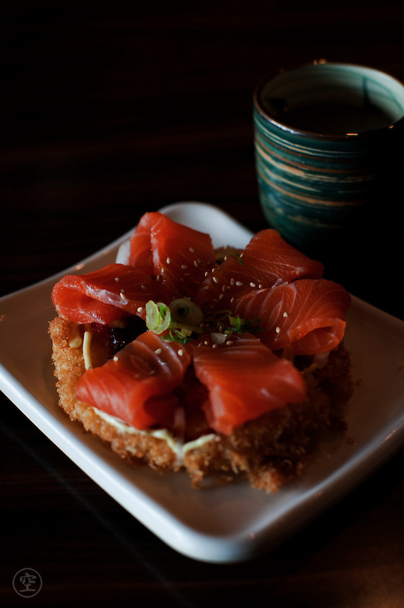 Sushi pizza- a north American invention - with deep fried sushi rice topped with fresh salmon sashimi at a Japanese restaurant in Toronto.