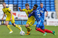 Wes Thomas of Oxford United (centre) looks for a way past Jermaine Anderson of Peterborough United (right) during the Sky Bet League 1 match between Peterborough and Oxford United at the ABAX Stadium, London Road, Peterborough, England on 30 September 2017. Photo by David Horn.