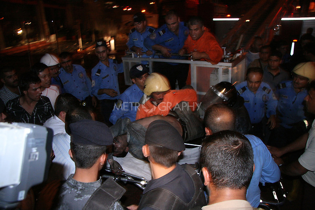 SULAYMANIYAH, IRAQ: Fireman take an injured resident to an ambulance on July 15, 2010...At least 41 people, including several foreign nationals, died in a hotel fire in the city of Sulaymaniyah in northern Iraq.  Another 23 people were injured in the fire on Thursday at the Soma Hotel in the central area of the city.<br /> <br /> Photo by Rawsht Twana