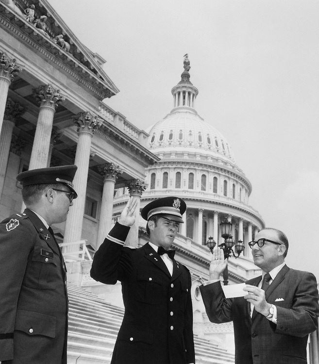 Rep. Joe Waggonner, D-La., is shown above on the steps of the Capitol in Washington administering the official oath of acceptance into the United States Army to Lieutenant to Henry Burns of Shongaloo, Louisiana. Major Clifford Eby, former Professor Military of Science at Northwestern State University, looks on at left. Henry Burns, who graduated from Northwestern State University recently has been working in Washington since February of this year as an Assistant Doorkeeper in the House of Representatives. (Photo by CQ Roll Call)