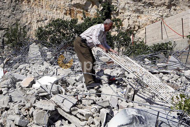 A Member of the Palestinian Ghaith family collects an iron door from the rubble of his home after it was demolished by Jerusalem municipality workers in the mostly Arab east Jerusalem neighbourhood of al-Tur on April 29, 2013. Palestinian homes built without an Israeli construction permit are often demolished by order of the Jerusalem municipality. Photo by Sliman Khader