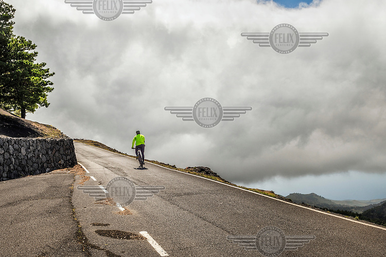 A man rides a bicycle up a mountain road with thick cloud billowing up ahead of him. /Felix Features