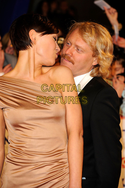EMMA WILLIS & LEIGH FRANCIS.National Television Awards at the O2 Arena, London, England..January 26th 2011.arrivals NTA NTAs half length griffiths gold brown beige one shoulder long maxi dress black suit jacket profile moustache mustache facial hair puckering kiss kissing .CAP/FIN.©Steve Finn/Capital Pictures.