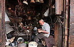 Palestinian man, Abu Hani al- Masawabi, 68, works on the manufacture and maintenance of a traditional kerosene and cooking utensils at his shop in Gaza City on June 29, 2019. Photo by Mahmoud Ajjour