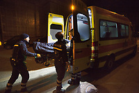 Switzerland. Canton Ticino. Lugano. Night scene for a medical emergency intervention. A man lying down on an emergency medical stretcher is being transported by ambulance. Paramedics team need to bring urgently a man with drug abuse to the hospital. Four paramedics wear blue uniforms and work for the Croce Verde Lugano. Both men and the woman (L) are professional certified nurses, the other man (R) is a volunteer specifically trained in emergency rescue. The Croce Verde Lugano is a private organization which ensure health safety by addressing different emergencies services and rescue services. Volunteering is generally considered an altruistic activity where an individual provides services for no financial or social gain to benefit another person, group or organization. Volunteering is also renowned for skill development and is often intended to promote goodness or to improve human quality of life. 20.01.2018 © 2018 Didier Ruef