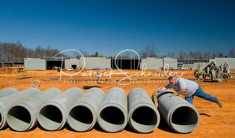 02/22/07:  A construction worker prepares cement pipes for installation during expansion/construction of a Charlotte-area shopping center. Charlotte, NC, is one of the country's fastest-growing cities. ..By Patrick Schneider- Patrick Schneider Photography.
