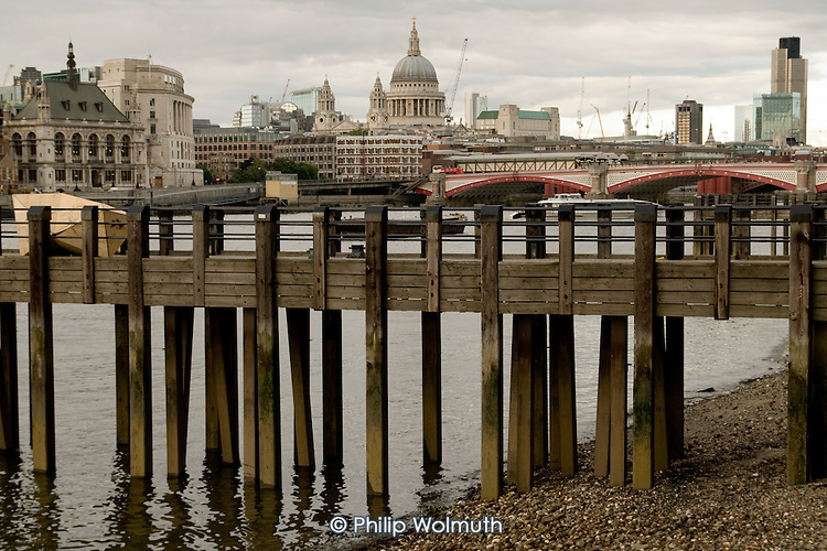 Wooden jetty on the south bank of the River Thames with the City of London, St Paul's Cathedral and the Natwest Tower