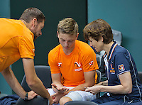 Switserland, Genève, September 16, 2015, Tennis,   Davis Cup, Switserland-Netherlands, Practise Dutch team, team docor Babette Pluim and fysio Edwin Visser treating Tim van Rijthoven for a blister<br /> Photo: Tennisimages/Henk Koster