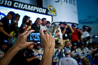 """A fan """"zeros-in"""" on Rick Hendrick, Chad Knaus and Jimmie Johnson on the podium with her point and shoot camera during the championship celebration."""