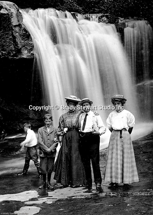 Stewart Township:  View of the Stewart family, Homer Jr, Alice, Homer, Helen and a Brady cousin posing for a photo in front of a water fall in Bear Run Creek 1905.  Stewart family went to visit Brady family relatives that lived in Stewart Township.
