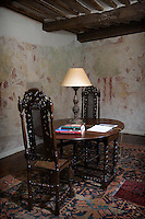 In the master bedroom a Jacobean table and pair of high-backed chairs have been placed in front of a section of the 16th century wall paintings
