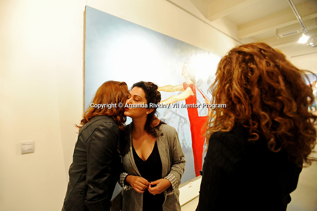 Visitors greet Azerbaijani painter Tora Agabekova (center) at her art opening in the old city of Baku, Azerbaijan on October 7, 2011.