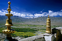 Golden sculptures on the walls of the Thikse Gompa Monastery with scenic view of mountains in the background, Ladakh, India.