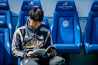 LEICESTER, ENGLAND - APRIL 18:  Ki Sung-Yueng of Swansea City  reads the programme prior to the Premier League match between Leicester City and Swansea City at The King Power Stadium on April 18, 2015 in Leicester, England.  (Photo by Athena Pictures/Getty Images)