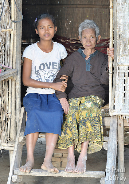 Srey Mao, 14, with her grandmother Nou in Khnach, a village in the Kampot region of Cambodia. Along with another sister, Srey Mao lives with and takes care of her aging grandmother. Her parents died of AIDS.