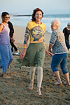 Woman instructor leads senior adults in exercise and dance class on Playa Del Rey Beach at sunset in Los Angeles, California