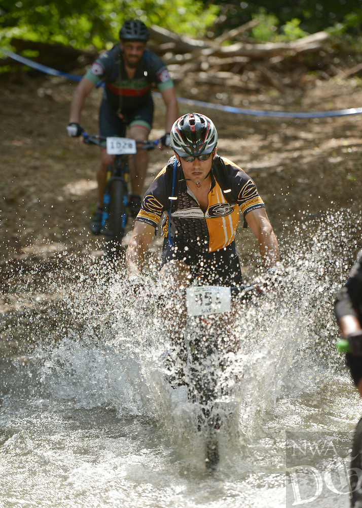 NWA Democrat-Gazette/BEN GOFF @NWABENGOFF<br /> Steven Blocker, a category 3 racer from Emporia, Kan., fords a creek Sunday, July 16, 2017, during cross country races on the final day of the 19th annual Fat Tire Festival at Lake Leatherwood City Park in Eureka Springs.