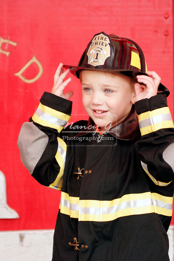 A young future firefighter Fire Chief posing with the Fire Department personnel uniform on in front of a engine backdrop at a safety fair