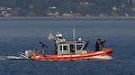 A United State Coast Guard Patrol boat performs escort service for the Washington State Ferry Issaquah near Seattle on August 20, 2009.  The personnel and boats, from the 13th Coast Guard District, provide protection from possible terrorists attacks in support of the Homeland Security for ferries operating from Seattle area ferry terminals to those on the Kitsap Peninsula, Vashion Island, and Bainbridge Island.    © 2009. All Rights Reserved. Jim Bryant