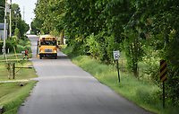 NWA Democrat-Gazette/DAVID GOTTSCHALK A Farmington Public Schools bus picks up a student Tuesday, May 7, 2019, on Wesley Stevens Road before the intersection with Gibson Hill Road. Washington County is working with local school districts to identify and improve some of the narrow, dangerous county roads that double as bus routes.