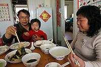Li Fang (gauche) aide sa petite-fille Li Siqi (centre) à manger, sous l'oeil de Gao Cuilan (droite) pendant le déjeuner, à Baoshan, près de Shanghai, le 7 mai 2008. Photo par Lucas Schifres/Pictobank