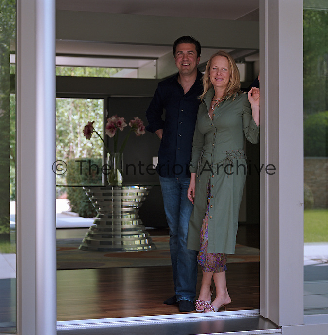 Art dealer and curator Anna Belayeva and her husband Michael Schmidt stand at the entrance of their home