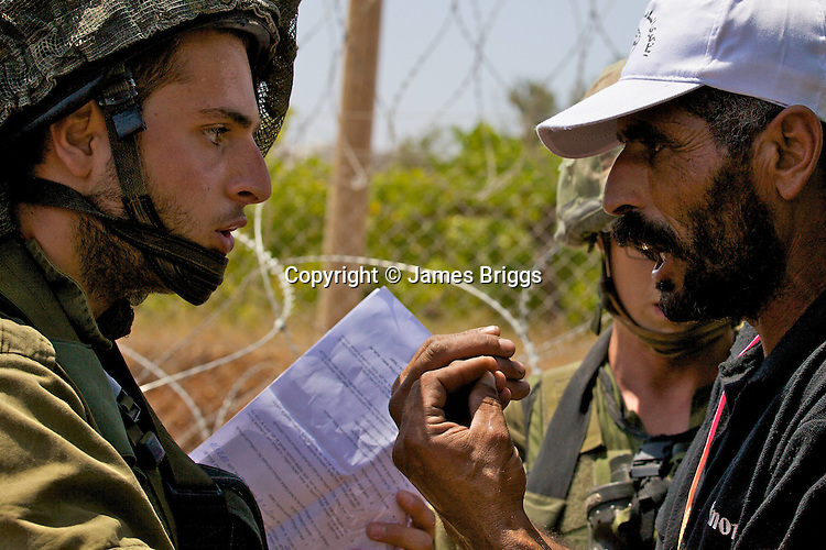 An Israeli soldier brandishing a document classifying the area as a closed military zone is confronted by a Palestinian protester & village resident during a non-violent demonstration in the West Bank village of Beit Ummar near Hebron on 10/07/2010.