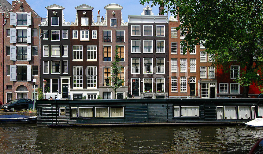 Raw of houses and a boathouse (flat/home in a boat) in Amsterdam, The Netherlands