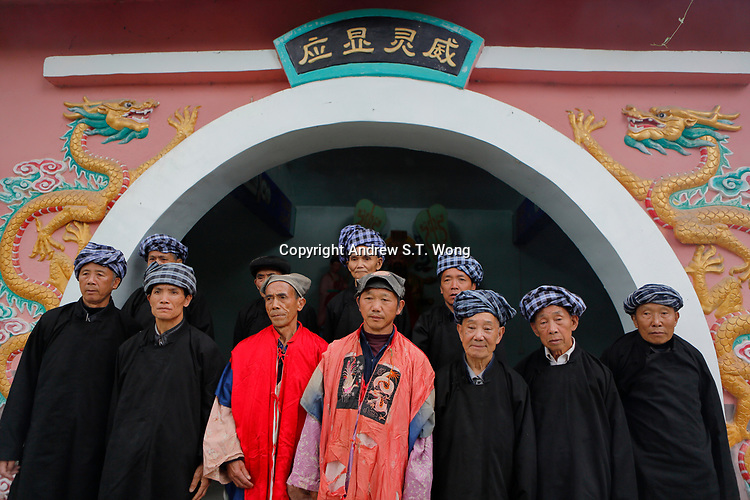 Bouyei priests gather outside a shrine before performing rites to celebrate the Lunar March 3rd Festival at Wangmo County in China's southwestern Guizhou Province, April 2019.