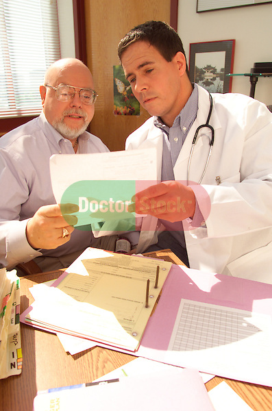 young male doctor consulting with older, elder male patient, both sitting at desk in doctor's office