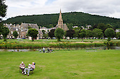A man and a woman reading by the River Tweed in Peebles, Scotland.