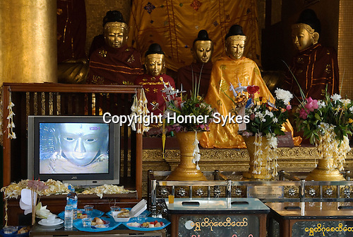 Shwedagon Paya. Offering left by pilgrims to one of many Buddha's. Yangon Rangoon  Myanmar Burma 2006.