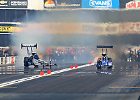 Nov 11, 2018; Pomona, CA, USA; NHRA top fuel driver Leah Pritchett (left) goes sideways as she smokes the tires alongside Bill Litton during the Auto Club Finals at Auto Club Raceway. Mandatory Credit: Mark J. Rebilas-USA TODAY Sports