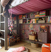 A girl's bedroom with a painted green ceiling and pink floral pattern wallpaper. A ladder leads up to a single bed under which is shelving for books and other items.