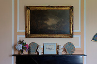 A gilt-framed painting of a stormy landscape hangs above busts of Queen Victoria and Prince Albert on a bedroom mantelpiece