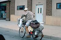 Homeless man age 42 gathering valuable items on his bike.  St Paul Minnesota USA