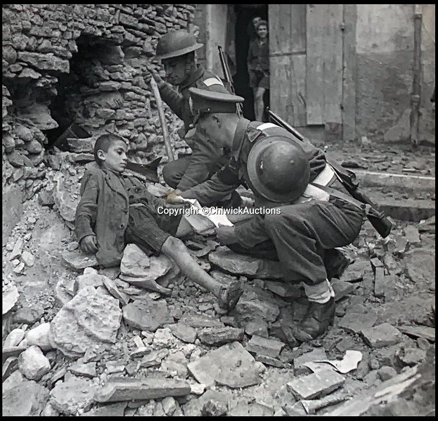 BNPS.co.uk (01202 558833)<br /> Pic:  ChiswickAuctions/BNPS<br /> <br /> Allies helping an Italian child following a shell raid on Monte Cassino.<br /> <br /> Remarkable previously unseen photos documenting the momentous closing stages of World War Two and its historic aftermath have come to light.<br /> <br /> They were taken by Sergeant Charles Hewitt, of the Army Film and Photographic Unit, who later went on to work for the Picture Post and the BBC.<br /> <br /> He was present at many of the important offensives of 1944 and '45 including the Battle of Monte Cassino during the Italian Campaign and the Allies advance into Germany following the D-Day invasion.