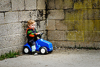 Little boy playing on a push along car