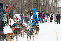 Ramey Smyth and team run past spectators on the bike/ski trail near University Lake with an Iditarider in the basket and a handler during the Anchorage, Alaska ceremonial start on Saturday, March 7 during the 2020 Iditarod race. Photo © 2020 by Ed Bennett/Bennett Images LLC