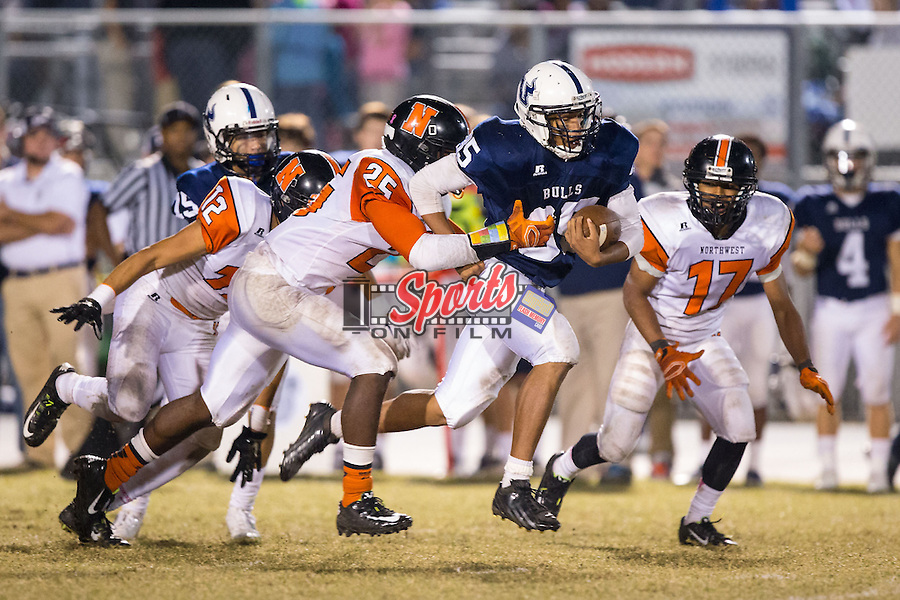 Remington Peters (35) of the Hickory Ridge Ragin' Bulls is tackled by Anthony Caldwell (25) of the Northwest Cabarrus Trojans at Hickory Ridge High School on October 17, 2014 in Harrisburg, North Carolina.  The Ragin' Bulls defeated the Trojans 34-6.  (Brian Westerholt/Sports On Film)