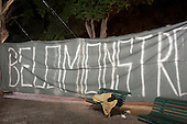 """Praça Tiradentes, Rio de Janeiro, Brazil. A homeless man sleeps on a park bench in front of a hand-painted banner reading """"Belo Monstro"""" as part of a campaign against the Belo Monte hydroelectric dam during the screening of the film """"Belo Monte: Declaration of War""""."""