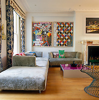 The corner of the living room is furnished with a grey velvet modular sofa by Francesco Bifare and decorated with impressive contemporary works of art including two large drawings by Keith Tyson