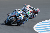 Vittorio Iannuzzo (ITA) riding the BMW S1000 RR (31) of the Grillini DENTALMATIC SBK Team rounds turn 6 ahead of Leon Haslam (GBR) riding the Honda CBR1000RR (91) of the Pata Honda World Superbike Team  during a qualifying session on day one of round one of the 2013 FIM World Superbike Championship at Phillip Island, Australia.
